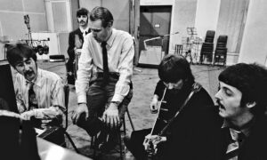A photo of George Martin coaching the Beatles.