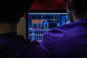 A photo of two people looking at a readout of an equalizer. In this article we discuss my favorite equalizers for electronic music.